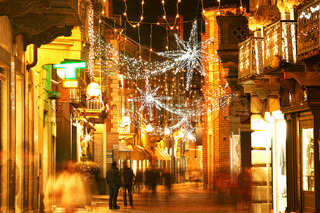 Alba old town central street with opened shops, bars and stores illuminated and decorated for Christmas and New Year holidays