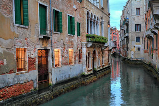 Small canal among old brick traditional venetian houses with illuminated windows at evening in Venice, Italy