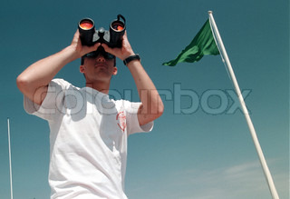 Low angle view of a lifeguard looking through an binoculars against clear sky