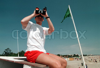 Lifeguard looking through binoculars with people on the beach