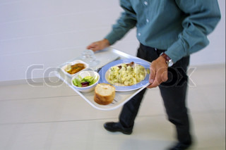 Low section of male student carrying food tray in canteen