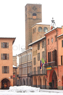 Vertical oriented image of cental square, city hall and ancient tower under the snow in Alba, Northern Italy.