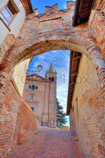 Vertical oriented image of church and medieval brick fortification wall and narrow cobbled street in town of Monticello D'Alba in Piedmont, Italy