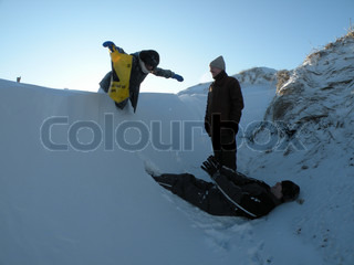 person about to fall into deep snow on another person waiting to catch her