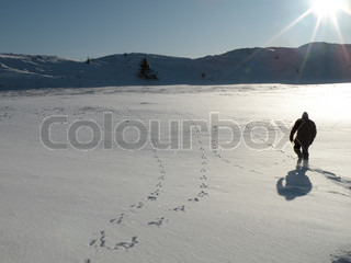 man going through deep snow in dune landscape