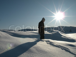 man standing in deep snow with sun in background