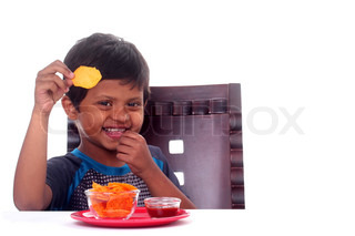 Happy & smiling Indian boy eating unhealthy chips The kid is school going 6 years old and the photo is taken on white background