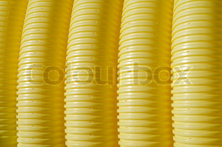 Industrial background - yellow plastic corrugated pipe close-up