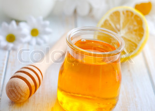 fresh honey in the glass bank and camomiles