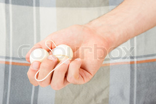 Hand holding white vaginal balls, isolated