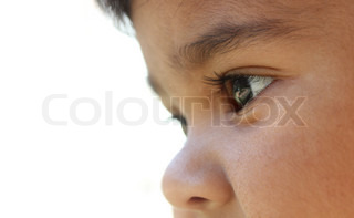 Extreme closeup of indian baby girl's face who looks like day dreaming or imagining or curiously looking at something