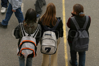 Rear view of college girls with backpacks walking on street