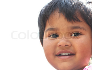Photo of pretty & happy indian girl child smiling & looking at the camera with toddler's innocence and a beautiful grin The child is of pre school/kinder-garten age