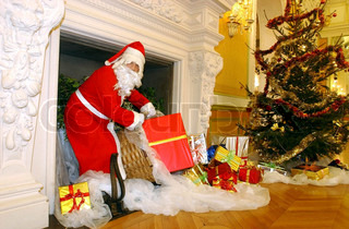 Santa Claus on the fireplace with presents