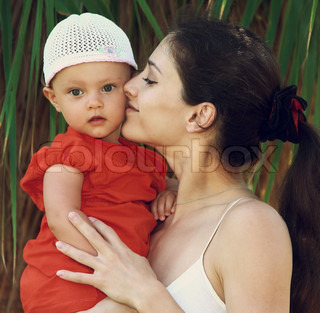 Mother kissing baby girl in hat holding on hands outdoors green trees background