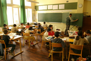 Students sitting in classroom while teacher writing on board