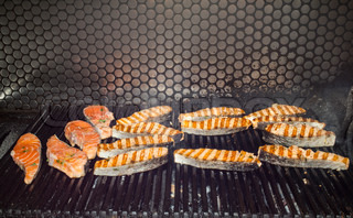 cooking salmon on the grill in the restaurant
