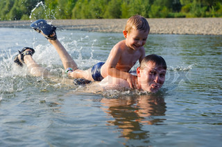 Young father and son swimming in river