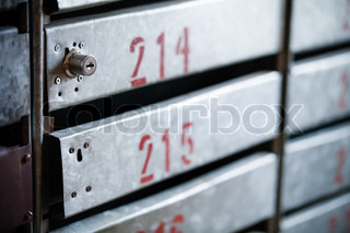 Old iron postboxes with locks and red apartment numbers