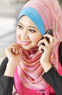 pretty Muslim girl using hand phone at cafe