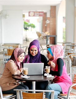 Pretty Muslim Girl using laptop with friends