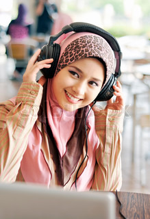 Pretty Muslim girl enjoy listening music from laptop at cafe