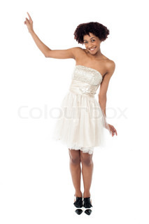Joyous fashion female model pointing upwards