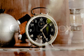 Vintage old alarm clock in glass closet as sepia tone