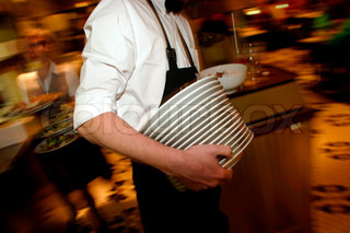 View of a waiter carrying plates