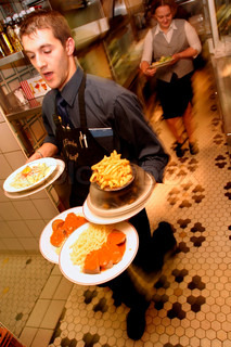 View of waiter carrying food plates