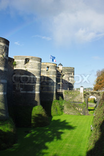 Towers and bridge of castle of Angers under rainbow, France and EU banner