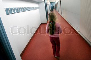 Rear view of a girl walking in a school corridor