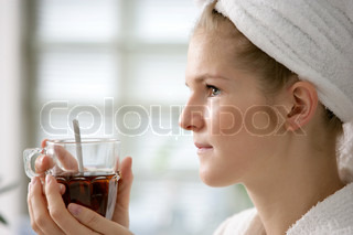A young woman in a wellness spa enjoying a cup of tea