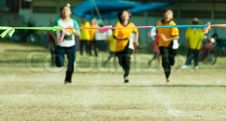 child girl sprinting to finish line in sport day of school