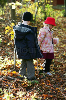 Children walking in the autumn forest