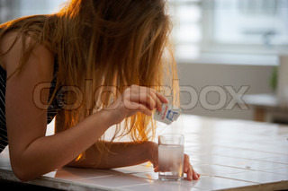 A woman with a hangover with a  fizzy water