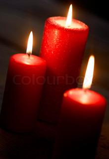 Tre brændende røde stearinlys på bordet