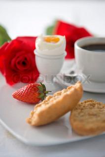 Romantisk morgenmad serveret på fad med kaffe, æg, brød, jordbær og en rød rose