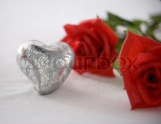Et sølvhjerte og røde roser på hvid baggrund