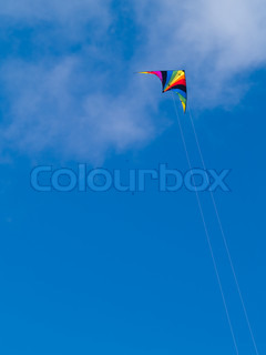 A rainbow colored stunt kite against a blue sky with wispy clouds