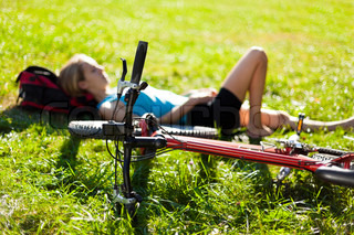 Young girl cyclist enjoying relaxation lying in the fresh green grass