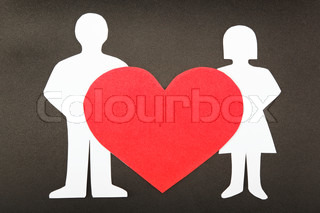 Silhouettes of men, women and heart cut out of paper on a black background Happy couple in love