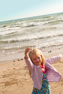 Dancing little girl on the beach
