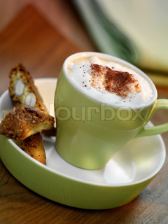 A cup of cappuccino and biscuits
