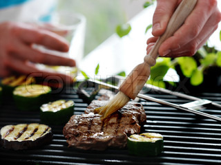A woman brushing marinade ouil on barbeque steak