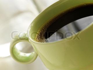 Nærbillede af en en grøn kop med sort kaffe