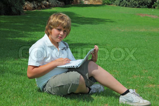 The beautiful boyplayed on laptop on a lawn