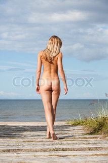 Young nude woman goes to the sea