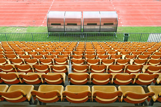 Coach and reserve benches with yellow seats in football stadium Back Perspective