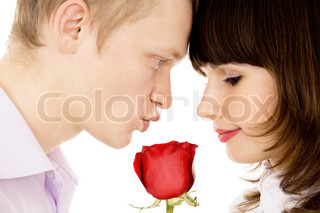 a guy and a girl holding a rose and look at each other